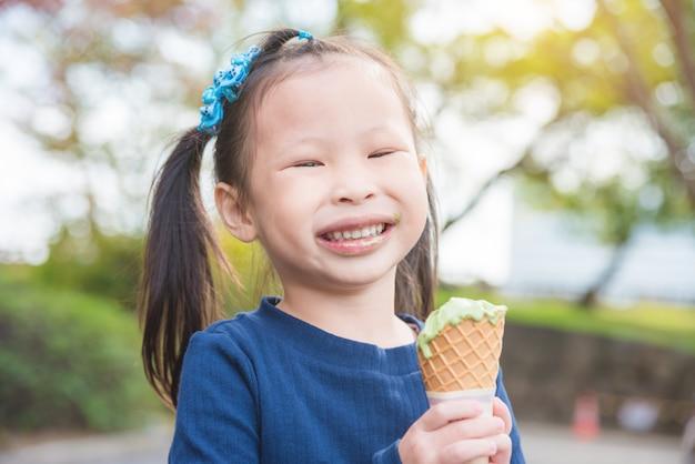 Piccola ragazza asiatica che sorride con la bocca sporca mentre mangiando il gelato in parco