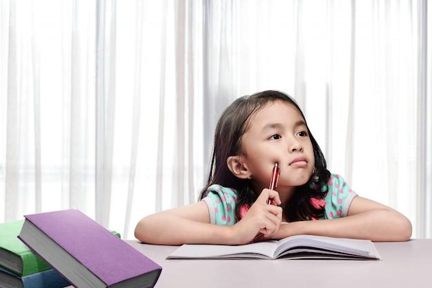 Piccola ragazza asiatica con libro e penna pensando quando si fa i compiti