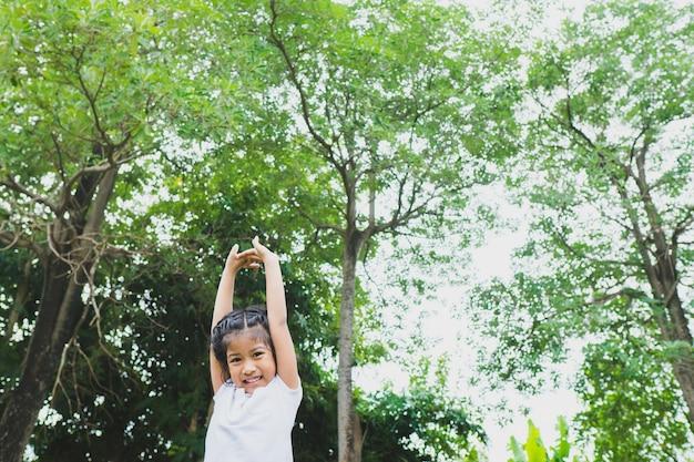Piccola ragazza asiatica del bambino che fa yoga nel parco pubblico.