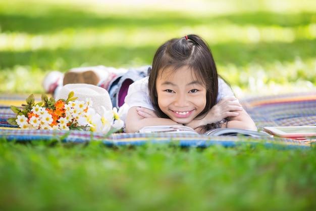 Piccola ragazza asiatica divertente che legge e che impara con il pc della compressa