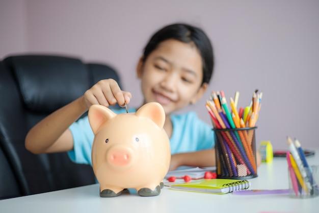 Piccola ragazza asiatica felice che mette la moneta dei soldi nel porcellino salvadanaio