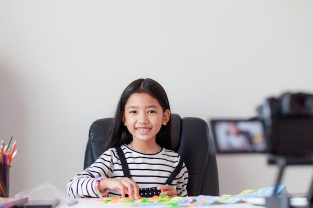 Piccola ragazza asiatica felice che si siede al tavolo bianco e streaming live per i social media con felicità