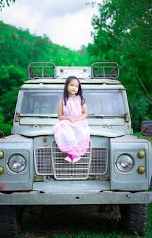 Piccola ragazza asiatica in vestito che si siede sull'auto d'epoca nel parco