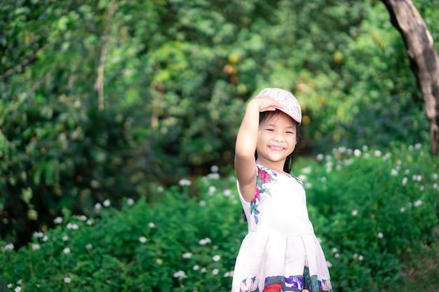 Piccola ragazza asiatica in vestito che sorride mentre indossa il cappuccio nel parco