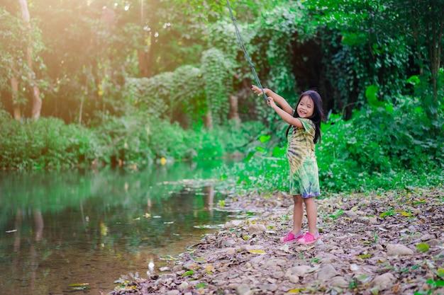 Piccola ragazza asiatica preparando a saltare nel fiume dalla corda oscillante