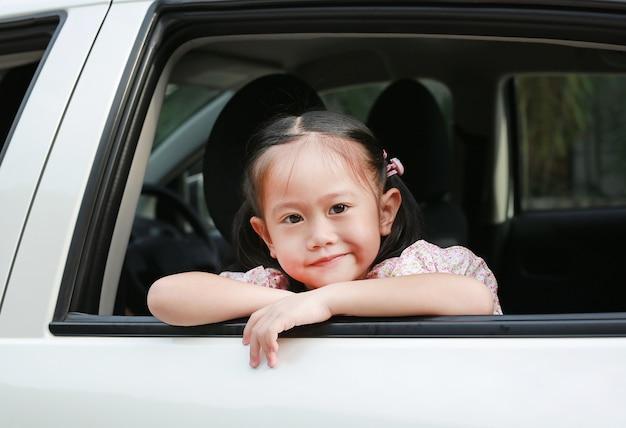 Piccola ragazza asiatica sorridente che guarda macchina fotografica dalla finestra dell'automobile bianca.