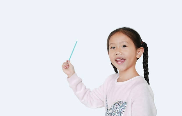 Piccola ragazza asiatica sorridente che indica sul presente qualcosa
