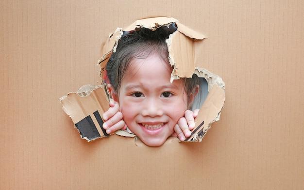 Piccola ragazza asiatica sorridente del bambino che guarda attraverso il foro su cartone con lo spazio della copia intorno.