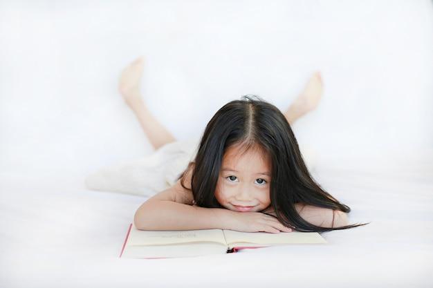 Piccola ragazza asiatica sorridente del bambino con il libro dalla copertina rigida che si trova sul letto e che guarda macchina fotografica sopra fondo bianco.