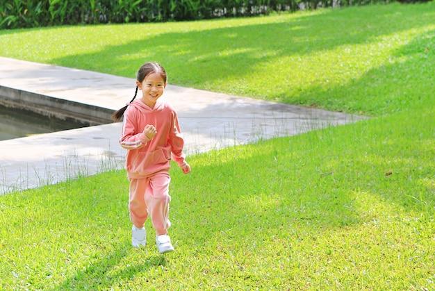 Piccola ragazza asiatica sorridente del bambino in tuta sportiva rosa che funziona nel giardino verde del prato inglese.