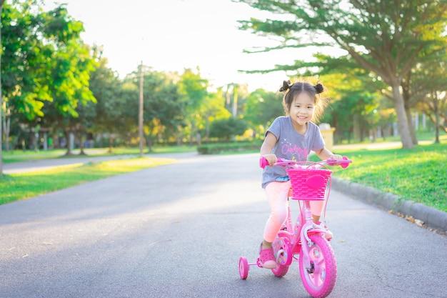 Piccola ragazza asiatica sveglia che guida una bicicletta per esercitarsi nel parco, sport dei bambini e stile di vita attivo