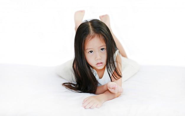 Piccola ragazza asiatica sveglia che si trova sul letto con l'esame della macchina fotografica sopra fondo bianco.
