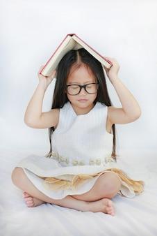 Piccola ragazza asiatica sveglia che si trova sul letto e sul libro di copertina rigida sulla sua testa e sugli occhi chiusi sopra fondo bianco.