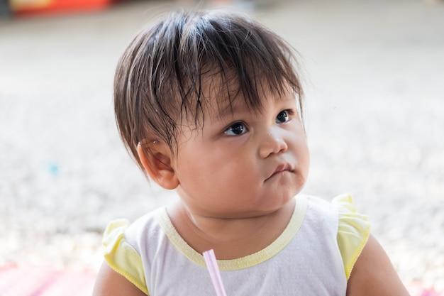 Piccola ragazza asiatica sveglia che succhia acqua dalle bottiglie