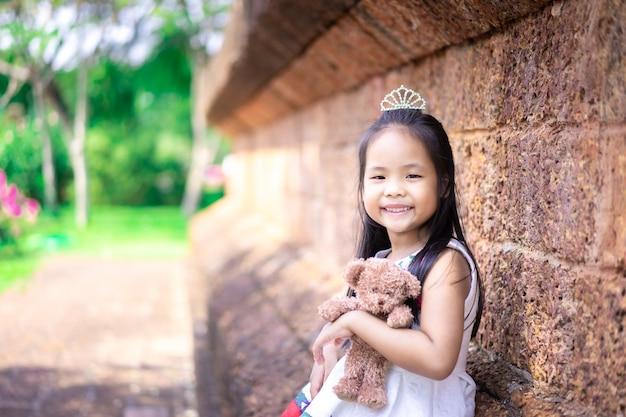 Piccola ragazza asiatica sveglia con una bambola nel parco