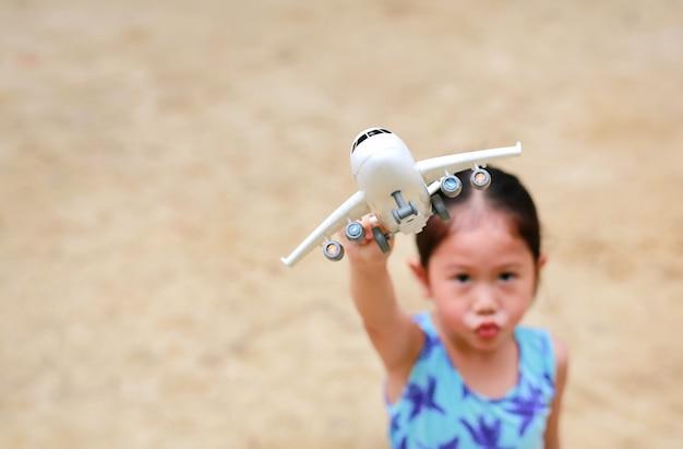 Piccola ragazza asiatica sveglia del bambino che gioca aeroplano del giocattolo nel giardino.