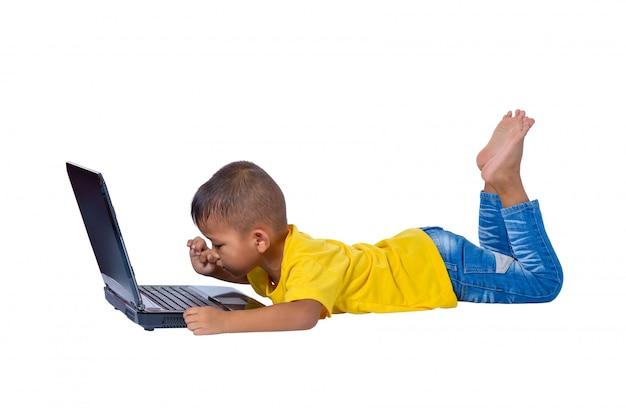 Piccola ragazza asiatica sveglia della ragazza che si trova sul pavimento che studia o che per mezzo del computer portatile isolato su fondo bianco