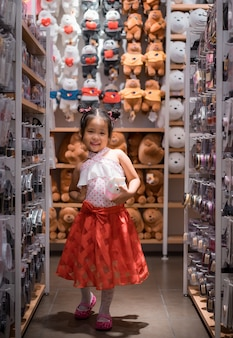 Piccola ragazza asiatica sveglia in vestito con una bambola in negozio