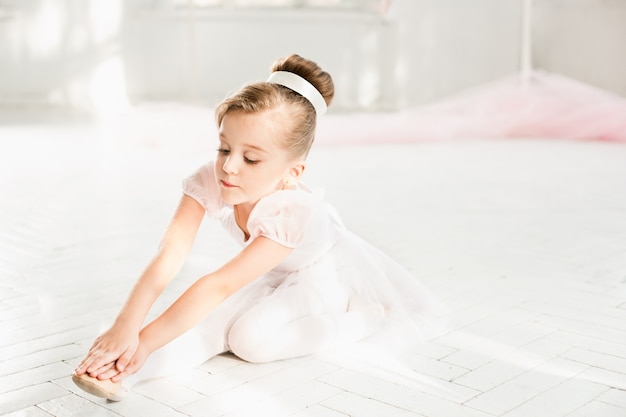 Piccola ragazza ballerina in un tutu. bambino adorabile che balla balletto classico in uno studio bianco.