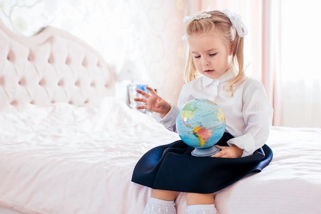 Piccola ragazza bionda adorabile in uniforme scolastica e golf bianchi che collocano su una berlina nella sua camera da letto e sconvolge il primo giorno di scuola.