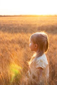 Piccola ragazza bionda carina in abito giallo nel campo di grano al tramonto con riflessi di sole