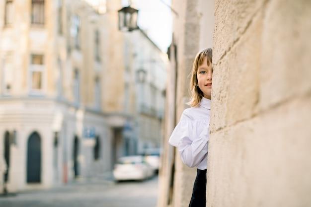 Piccola ragazza bionda caucasica sveglia in vestiti in bianco e nero, che propone alla macchina fotografica all'aperto nella vecchia via della città, nascondendo il suo fronte dietro il muro antico della costruzione