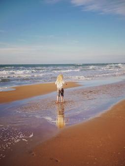 Piccola ragazza bionda che corre e che gioca su una spiaggia tropicale al tramonto durante le vacanze estive. infanzia giocosa. concetto di tempo libero e persone. nozione di rilassamento