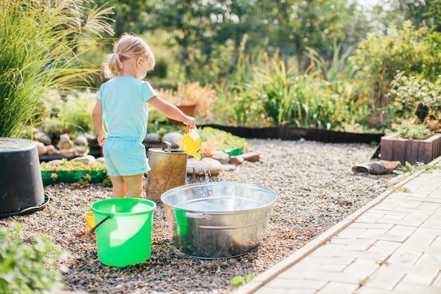 Piccola ragazza bionda che gioca al giardino con acqua in un bacino di latta. giardinaggio per bambini. divertimento acquatico all'aperto estivo. l'infanzia nel paese