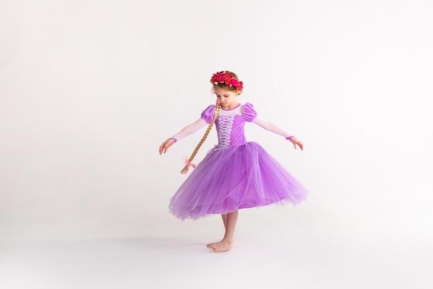 Piccola ragazza bionda che porta il vestito da principessa leggiadramente porpora su fondo bianco. costume per bambini per la festa di capodanno