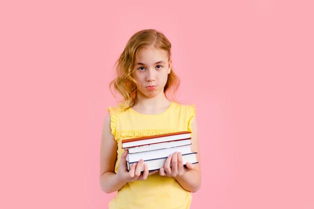 Piccola ragazza bionda che posa con i quaderni