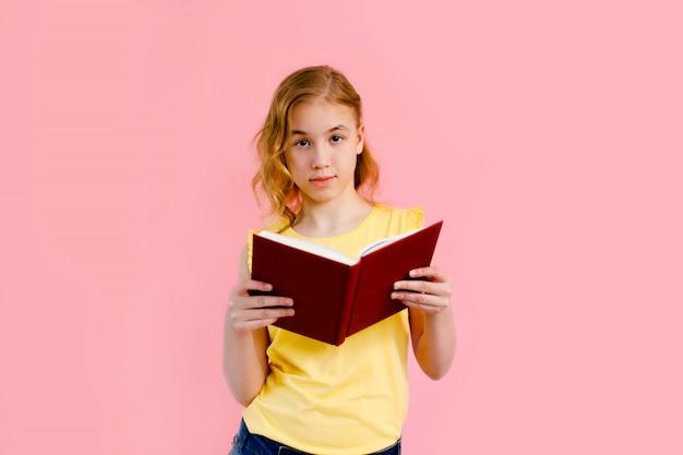 Piccola ragazza bionda che posa con il quaderno