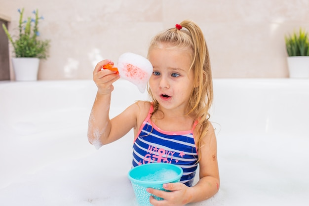 Piccola ragazza bionda che prende il bagno di bolla in bello bagno. igiene dei bambini. shampoo, trattamento per capelli e sapone per bambini. fare il bagno bambino in una grande vasca.