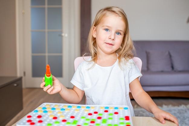 Piccola ragazza bionda che si siede ad una tavola a casa che gioca con un cacciavite del giocattolo