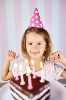 Piccola ragazza bionda che sorride in protezione di compleanno rosa una torta di compleanno del cioccolato con le candele