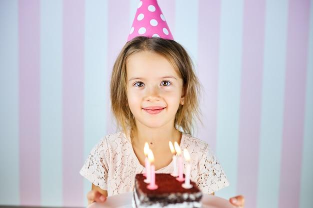 Piccola ragazza bionda che sorride in protezione rosa di compleanno, una torta di compleanno del cioccolato con le candele. la bambina festeggia il suo compleanno. buon compleanno.