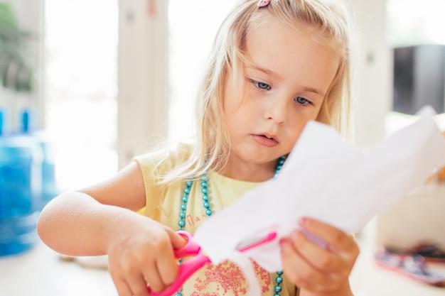 Piccola ragazza bionda con le forbici alla scuola materna. education.portrait di una bambina carina tagliando una carta.