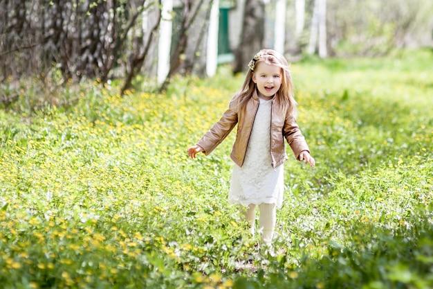 Piccola ragazza bionda del bambino in un vestito bianco che funziona sull'erba nel parco