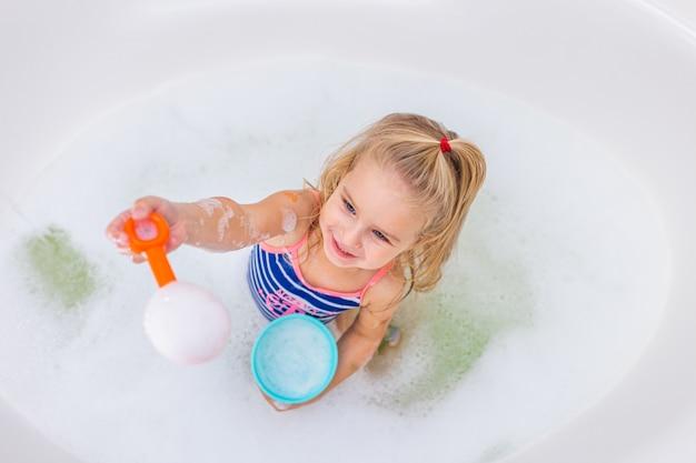 Piccola ragazza bionda divertente che prende il bagno di bolla in bello bagno. igiene dei bambini. shampoo, trattamento per capelli e sapone per bambini.