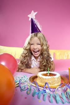 Piccola ragazza bionda felice in una festa di compleanno che ride con la candela