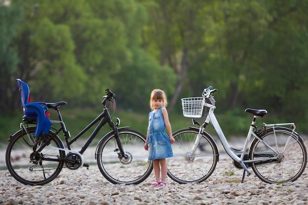 Piccola ragazza bionda graziosa in vestito blu che sta davanti alla bicicletta bianca con il secchio e quello nero con il seggiolino per bambini sul fondo vago degli alberi verdi. stile di vita attivo e concetto di ricreazione familiare.