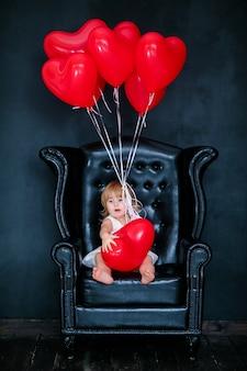 Piccola ragazza bionda in abito bianco con nastro rosso seduto sulla poltrona con palloncino cuore rosso il giorno di san valentino
