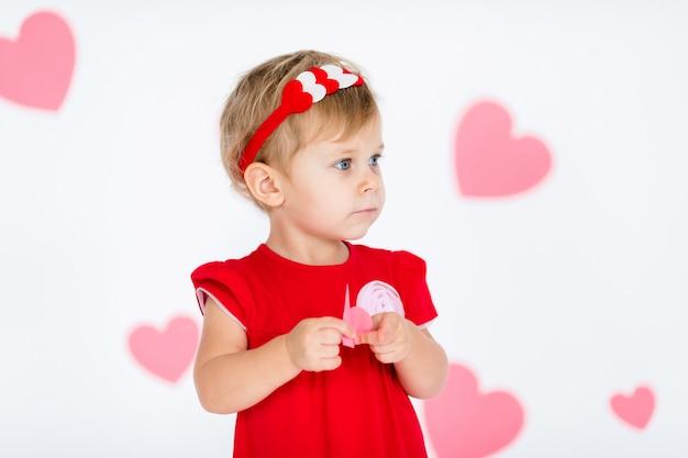 Piccola ragazza bionda in abito rosso con corona rossa con cuori su bianco con cuori rosa il giorno di san valentino