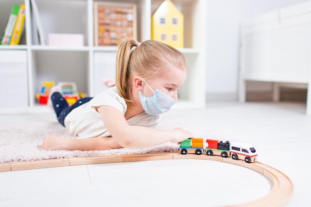 Piccola ragazza bionda in una mascherina medica che gioca con il trenino su un pavimento in una stanza chiara al hone durante la quarantena.