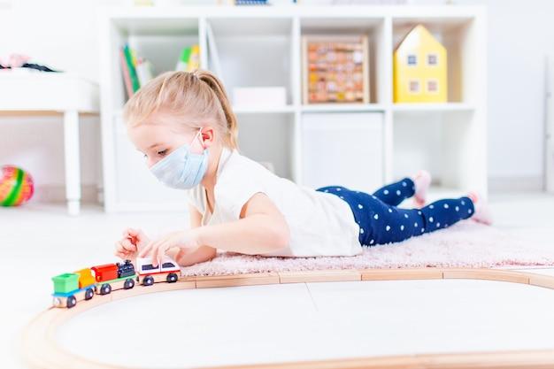 Piccola ragazza bionda in una mascherina medica che gioca con il trenino su un pavimento in una stanza leggera a casa durante la quarantena.