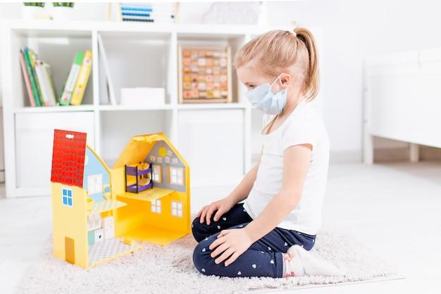 Piccola ragazza bionda in una mascherina medica che gioca con la casa del giocattolo su un pavimento in una stanza chiara a casa durante la quarantena.