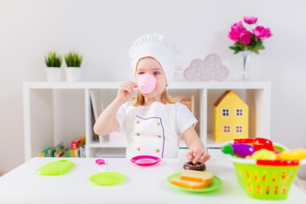 Piccola ragazza bionda in uniforme bianca del cuoco che gioca con la frutta e le verdure del giocattolo a casa, nell'asilo o nella scuola materna. attività di gioco da giocare con un bambino a casa