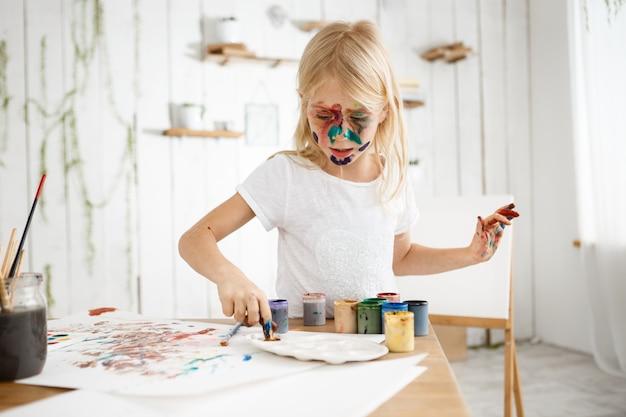 Piccola ragazza bionda occupata e concentrata sulla miscelazione di vernice sulla tavolozza.