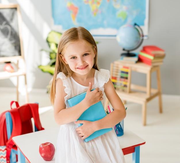 Piccola ragazza bionda sorridente che si siede sullo scrittorio bianco e che tiene libro blu nella classe di scuola del sole