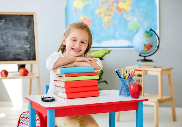 Piccola ragazza bionda sorridente che si tiene per mano sui libri nell'aula della scuola