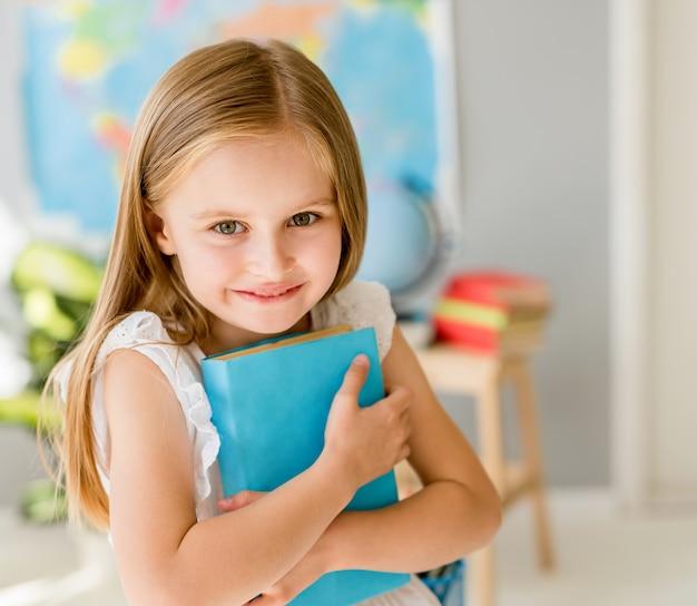 Piccola ragazza bionda sorridente che sta nell'aula della scuola
